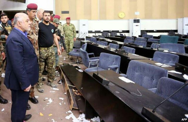 A handout image released by the press office of Iraqi Prime Minister Haider al-Abadi on May 1, 2016, shows him (L) looking at the damage after protesters stormed the Iraqi parliament building in Baghdad's fortified Green Zone area.