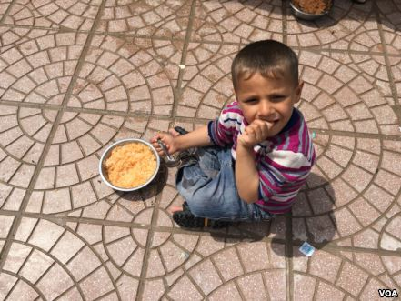 Young Iraqi boy eating rice with tomato sauce and potatoes supplied in a Kurdish-run camp for Iraqis fleeing IS, April 11, 2016. (S. Behn/VOA)