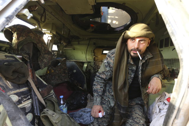 A Belgian fighter from the Democratic Forces of Syria holds a cigarette in his mouth inside a military vehicle in Ghazila village after taking control of the town from Islamic State forces in the southern countryside of Hasaka, Syria February 17, 2016. (Reuters)