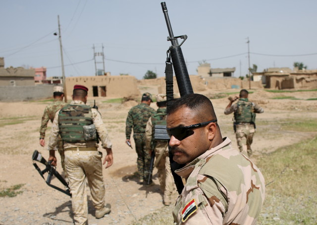 Iraqi soldier holds up his rifle as he walks with other soldiers in a village of Mahana some 60 km south of Mosul, Iraq, April 28, 2016. (Reuters)