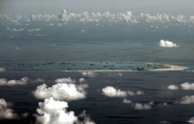 This aerial photo taken through a glass window of a military plane shows China's alleged on-going reclamation of Mischief Reef in the Spratly Islands in the South China Sea, May 11, 2015.