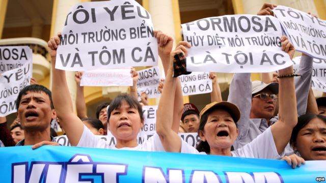 "Vietnamese protesters hold banners reading ""Formosa destroys the environment, which is a crime"" and ""I love the sea, shrimp and fish"" during a rally denouncing recent mass fish deaths in Vietnam's central province, in Hanoi, Vietnam, May 1, 2016."