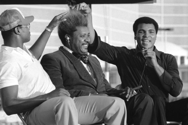 "Boxing great Muhammad Ali, right, and WBC heavyweight champion Larry Holmes, left, pull on promoter Don King?s hair during a TV taping of the ""Tomorrow,"" Sept. 29, 1980 in Las Vegas, a few days before they would square off for the heavyweight championship. (AP)"