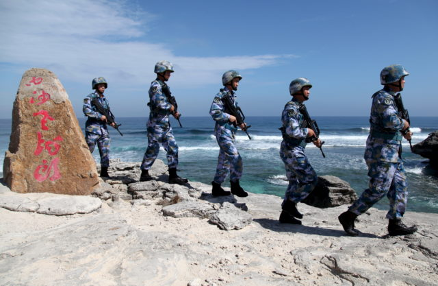 """Soldiers of China's People's Liberation Army (PLA) Navy patrol at Woody Island, in the Paracel Archipelago, which is known in China as the Xisha Islands, January 29, 2016. The words on the rock read, """"Xisha Old Dragon"""". Old Dragon is the local name of a pile of rocks near Woody Island. Picture taken January 29, 2016. (Reuters)"""