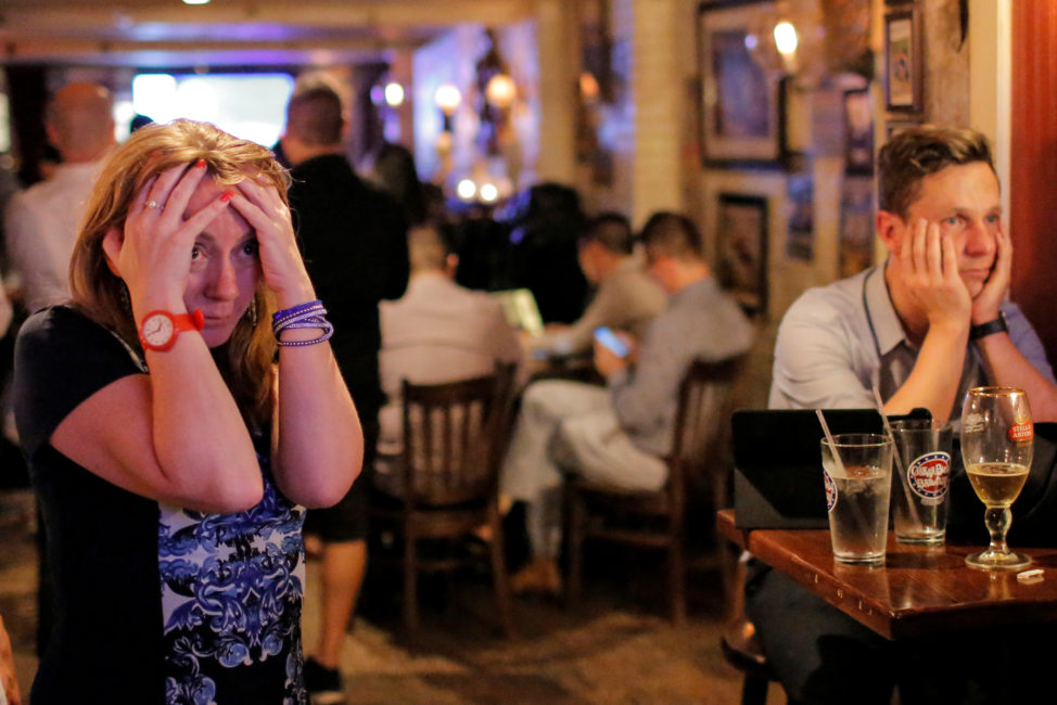 People gathered in The Churchill Tavern, a British themed bar, react as the BBC predicts Briatin will leave the European Union, in the Manhattan borough of New York, U.S., June 23, 2016. (Reuters)