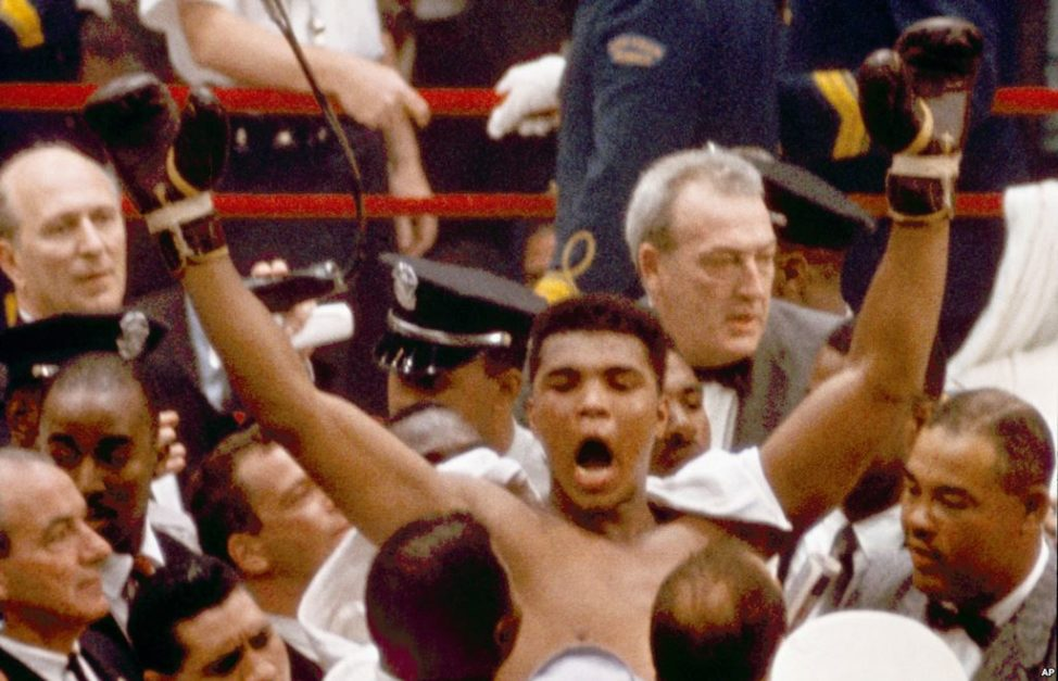 "Muhammad Ali, or Cassius Clay at the time, strikes a familiar pose as he shouts ""I am the greatest,"" as he leaves the ring, arms raised, following his defeat of former heavyweight boxing champion Sonny Liston in Miami Beach, Fla., February 25, 1964."