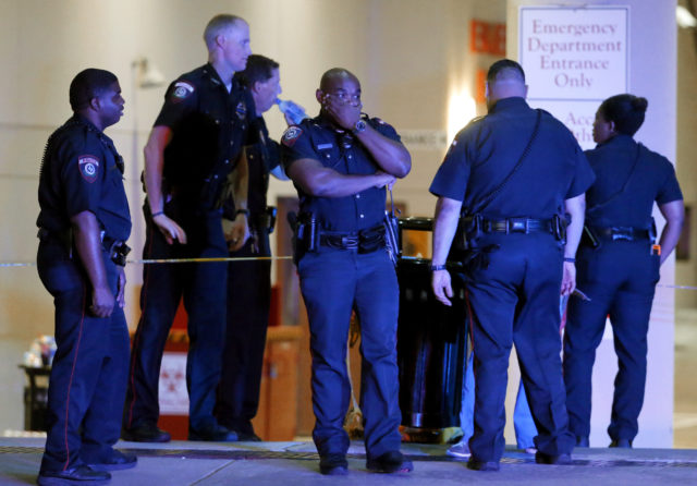 A Dallas police officer covers his face as he stands with others outside the emergency room at Baylor University Medical Center, Friday, July 8, 2016, in Dallas. Snipers opened fire on police officers in the heart of Dallas on Thursday night, killing some of the officers. (AP)
