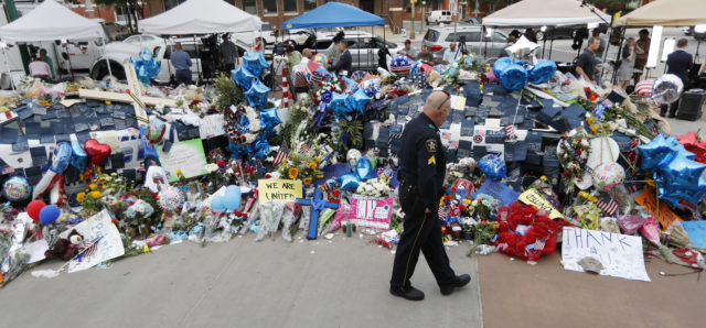 A policeman visits a makeshift memorial at the Dallas police headquarters, Monday, July 11, 2016, in Dallas. Five police officers were killed and several injured during a shooting in downtown Dallas July 7. (AP)
