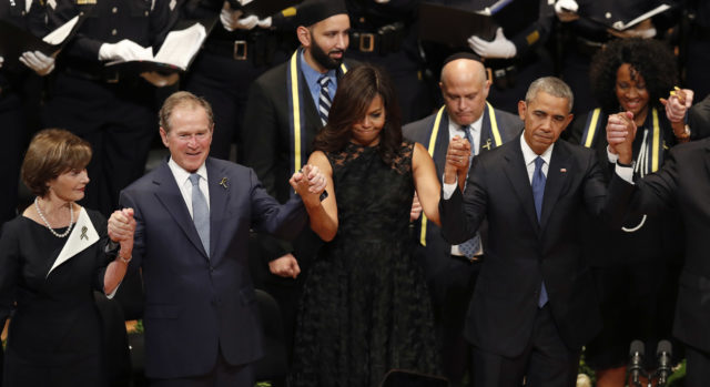 From left, former first lady Laura Bush, former President George W. Bush, first lady Michelle Obama and President Barack Obama join hands during a memorial service July 12, 2016 with the families of the five police officers killed in Dallas July 7. fallen police officers, Tuesday, (AP)