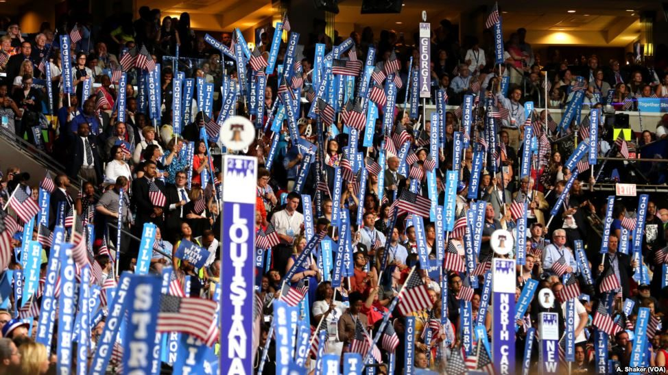 Hillary Clinton and Bernie Sanders supporters hold dueling signs on the fourth night of the Democratic National Convention in Philadelphia, July 28, 2016. (Ali Shaker/VOA)
