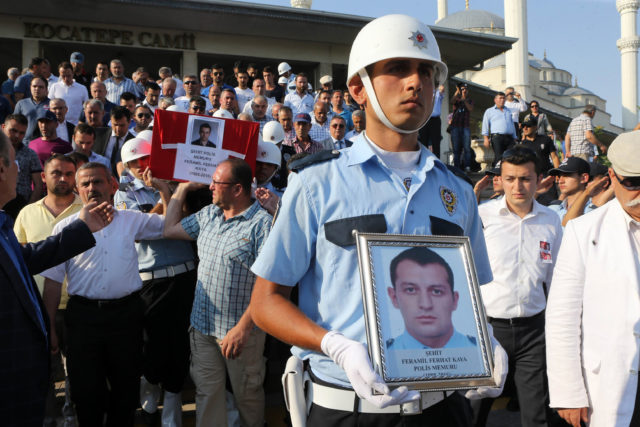 A Turkish Police officer holds a picture of one of the police officers killed during the failed July 15 coup attempt as other police officers carry the coffin during a funeral ceremony in Ankara on July 18, 2016.  Turkey launched fresh raids and sacked almost 9,000 officials today in a relentless crackdown against suspects behind an attempted coup that left over 300 people dead, as Western allies warned against reinstating the death penalty. / AFP PHOTO / ADEM ALTAN