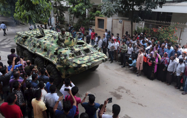 An armored vehicle drives past members of the press after an operation against militants who took hostages at a restaurant popular with foreigners in Dhaka, Bangladesh, Saturday, July 2, 2016.