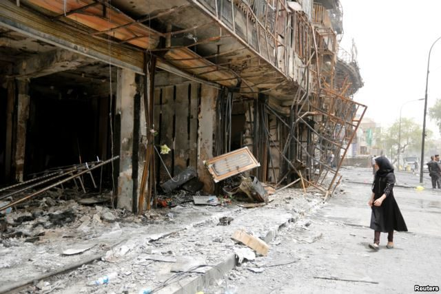 A girl walks past the site after a suicide car bomb attack at the shopping area of Karrada, a largely Shi'ite district, in Baghdad, Iraq, July 4, 2016.