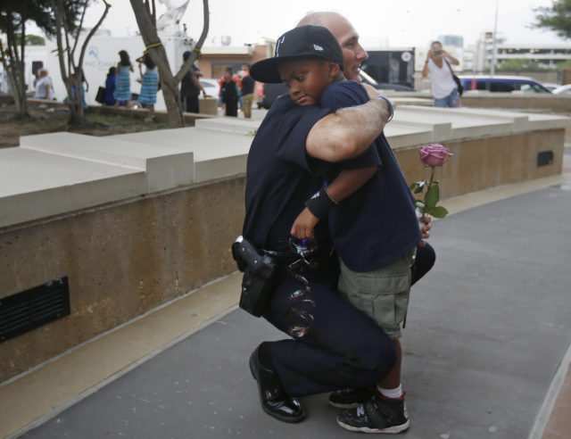 A Dallas Police officer hugs a child who came to pay respects at a makeshift memorial at Dallas Police Headquarters following the multiple police shootings in Dallas, Texas, U.S., July 9, 2016. (Reuters)