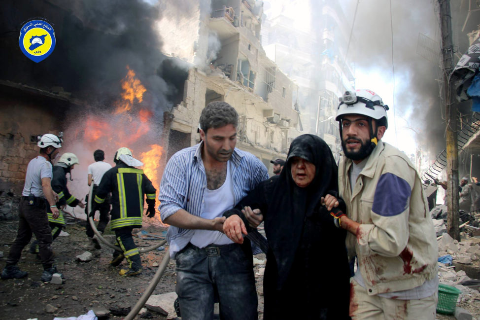 Residents trapped in rebel-controlled Aleppo are struggling to survive the crippling encirclement of their once thriving city. In this file photo taken on June 8, 2016, Syrian civil defense workers, right, helps an injured woman after warplanes attacked a street, in Aleppo, Syria. (Civil Defense Directorate in Liberated Province of Aleppo/AP)