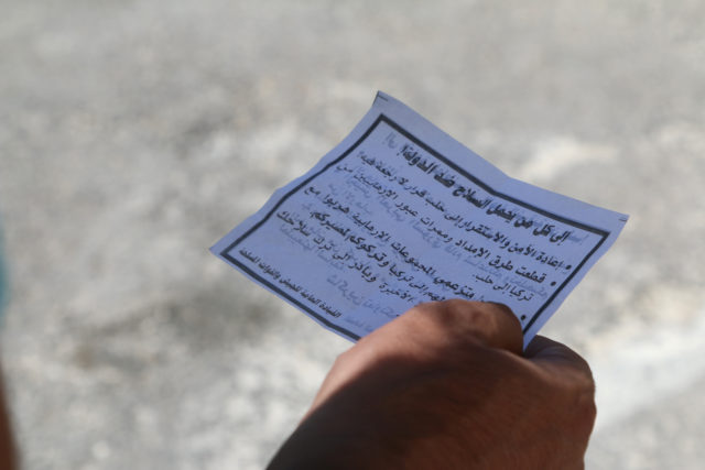 A man holds one of the leaflets dropped by the Syrian army over opposition-held Aleppo districts asking residents to cooperate with the military and calling on fighters to surrender, Syria July 28, 2016. (Reuters)