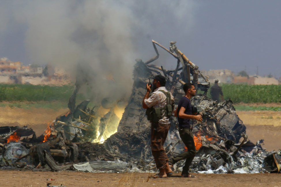 Men inspect the wreckage of a Russian helicopter that had been shot down in the north of Syria's rebel-held Idlib province, Syria August 1, 2016. (Reuters)