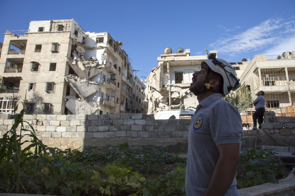 A Syrian rescuer looks towards the sky following an air strike in the rebel-held Ansari district in the northern Syrian city of Aleppo on September 23, 2016. Syrian and Russian aircraft pounded rebel-held areas of Aleppo, a monitor said, after the army announced a new offensive aimed at retaking all of the divided second city. (AFP)