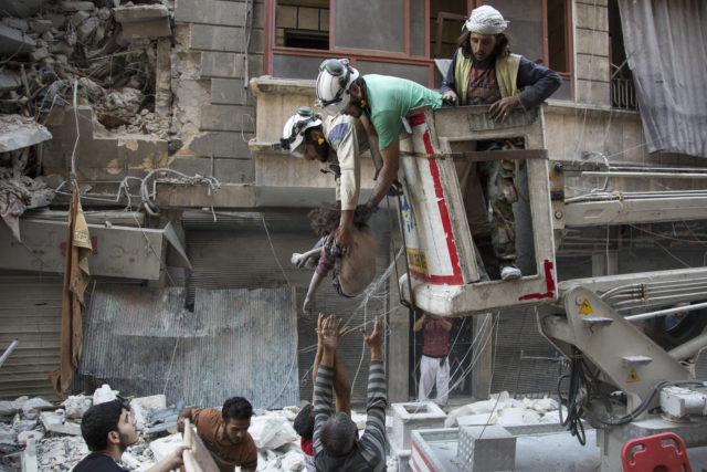 Syrian rescuers hand the body of a girl down to civilians on the ground after she was pulled from rubble of a budling following government forces air strikes in the rebel held neighborhood of Al-Shaar in Aleppo on September 27, 2016. Syria's army took control of a rebel-held district in central Aleppo, after days of heavy air strikes that have killed dozens and sparked allegations of war crimes. (AFP)