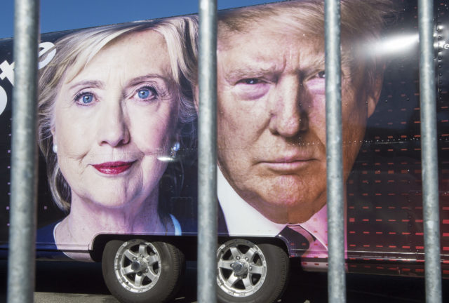 Large images of Democratic nominee Hillary Clinton and Republican nominee Donald Trump are seen on a CNN vehicle, behind a security fence, on Sept. 24, 2016, at Hofstra University, in Hempstead, New York, site of the first presidential debate on Sept. 26. (AFP)