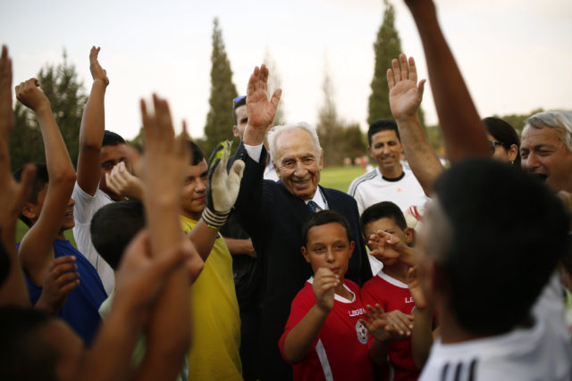 Former Israeli president Shimon Peres (C) is seen with Israeli and Palestinian children during an event opening a year of training of an Israeli-Palestinian soccer program launched by the Peres Center for Peace, in Kibbutz Dorot, outside the Gaza Strip, September 1, 2014. (Reuters)