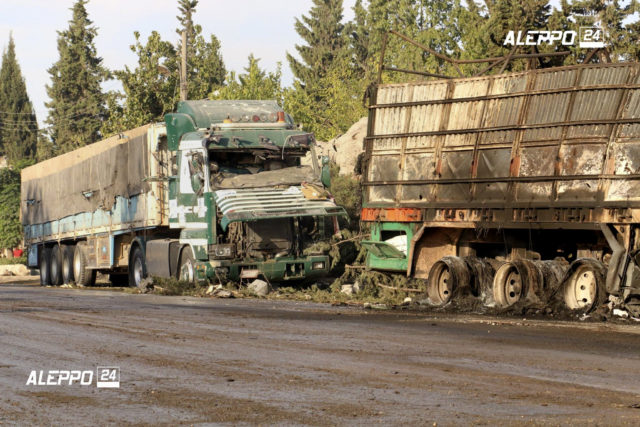 This image provided by the Syrian anti-government group Aleppo 24 news, shows damaged trucks carrying aid, in Aleppo, Syria, Sept. 20, 2016. A U.N. humanitarian aid convoy in Syria was hit by airstrikes Monday as the Syrian military declared that a U.S.-Russian brokered cease-fire had failed, and U.N. officials reported many dead and seriously wounded. (Aleppo 24 news via AP)