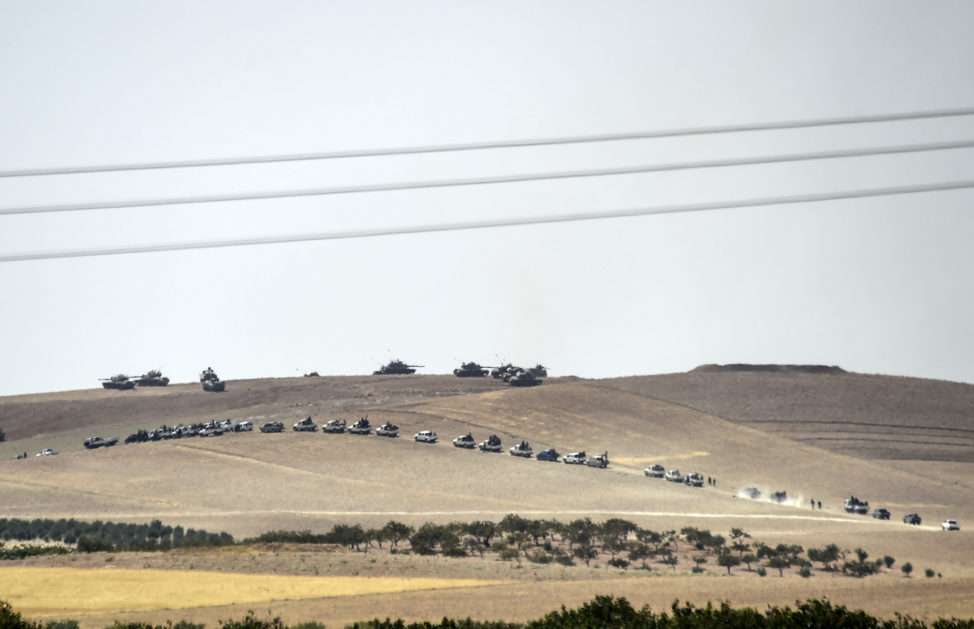 This picture taken from the Turkish Syrian border city of Karkamis in the southern region of Gaziantep, on August 24, 2016 shows Turkish army tanks and pro-Ankara Syrian opposition fighters moving two kilometres west from the Syrian Turkish border town of Jarabulus. (AFP)