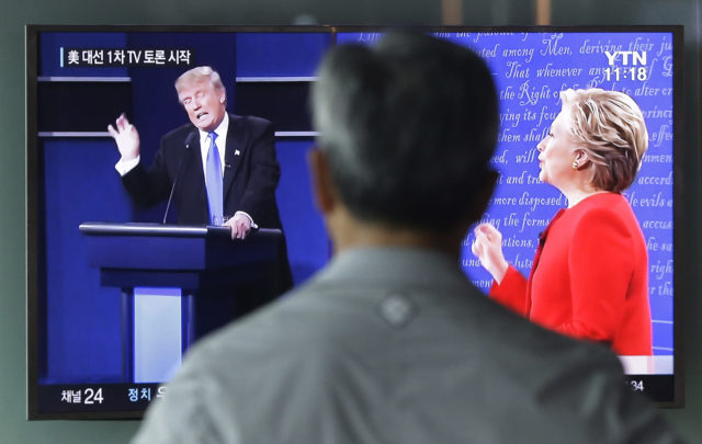 A man watches a TV screen showing the live broadcast of the U.S. presidential debate between Democratic presidential nominee Hillary Clinton and Republican presidential nominee Donald Trump, at Seoul Railway Station in Seoul, South Korea, Sept. 27, 2016. (AP)