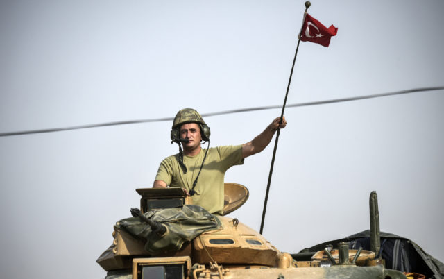 This picture taken around 5 kilometres west from the Turkish Syrian border city of Karkamis in the southern region of Gaziantep, on August 25, 2016 shows a soldier gesturing as Turkish Army tanks drive to the Syrian Turkish border town of Jarabulus. (AFP)