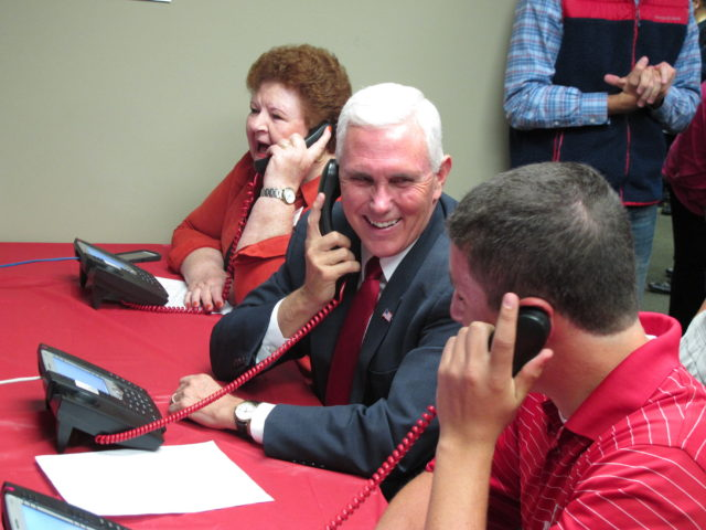 Republican vice presidential candidate Indiana Gov. Mike Pence makes phone calls along with campaign volunteers at a Republican party office on Sept. 27, 2016, in Fitchburg, Wis. (AP)