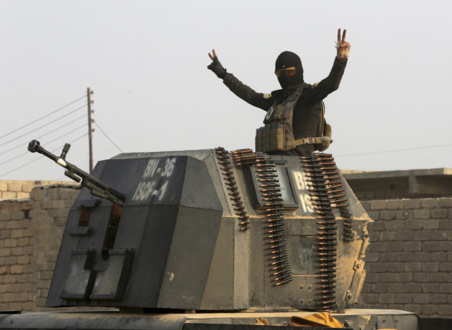 A member of Iraq's elite counterterrorism forces in a military convoy flashes a victory sign as forces advance toward Islamic State positions in the village of Tob Zawa, about 9 kilometers from Mosul, Iraq, Oct. 25, 2016. (AP)
