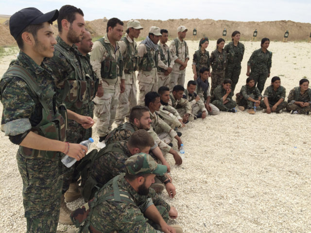 In this file photo taken May 21, 2016, members of what the U.S. calls the Syrian Democratic Forces gather after a training session at a firing range in northern Syria. Simultaneous attacks on the Islamic State-held city of Mosul in Iraq and Raqqa, the de facto IS capital across the border in eastern Syria, would make military sense: They would make it harder for the extremists to move reinforcements and deny them a safe haven. (AP)
