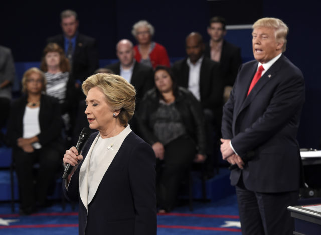 Democratic presidential nominee Hillary Clinton, left, talks as Republican presidential nominee Donald Trump watches her during the second presidential debate at Washington University in St. Louis,, Oct. 9, 2016. (AP)