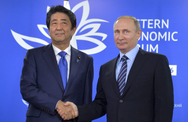 Russian President Vladimir Putin, right, and Japanese Prime Minister Shinzo Abe shake hands as they pose for a photo during their meeting in Vladivostok, Russia, Sept. 2, 2016. (AP)
