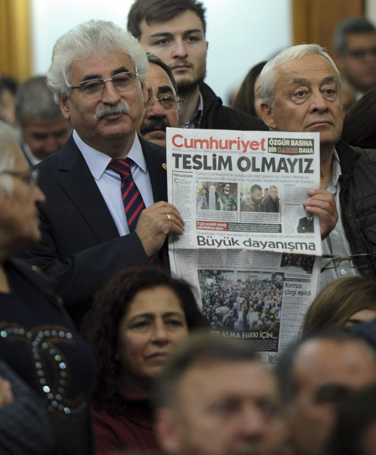 "A man holds a latest copy of Cumhuriyet with a headline that reads ""We Will Not Surrender"" in Ankara, Tuesday, Nov. 1, 2016. Turkey's prime minister on Tuesday shrugged off the European Union's criticism on media freedoms, following the detentions of at least 13 senior staff members of an opposition newspaper. (AP)"