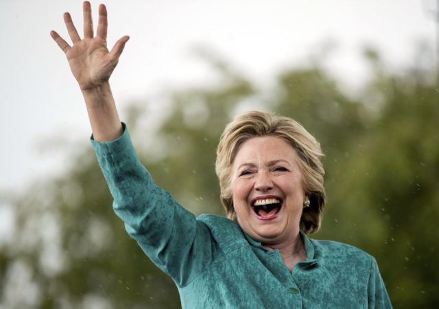 Democratic presidential candidate Hillary Clinton waves as she cuts her speech short due to rain at a rally at C.B. Smith Park in Pembroke Pines, Fla., Nov. 5, 2016. (AP)