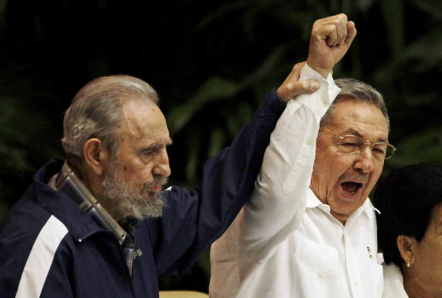 In this April 19, 2011 file photo, Fidel Castro, left, raises his brother's hand, Cuba's President Raul Castro, center, as they sing the anthem of international socialism during the 6th Communist Party Congress in Havana, Cuba. (AP)