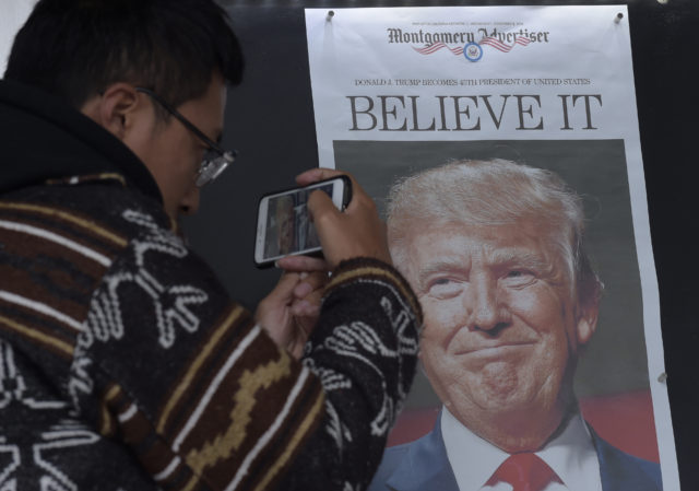 Zheng Gao of Shanghi, China, photographs the front pages of newspapers on display outside the Newseum in Washington, Nov., 9, 2016, the day after Donald Trump won the presidency. (AP)