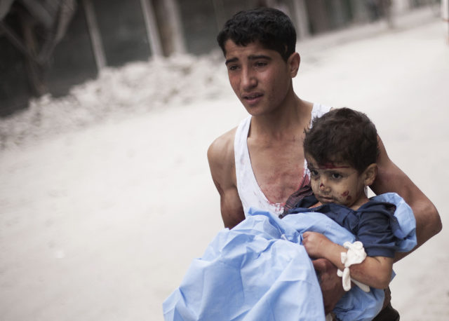 A Syrian young man holds a child wounded by Syrian Army shelling near Dar El Shifa hospital in Aleppo, Syria, Thursday, Oct. 11, 2012. (AP)