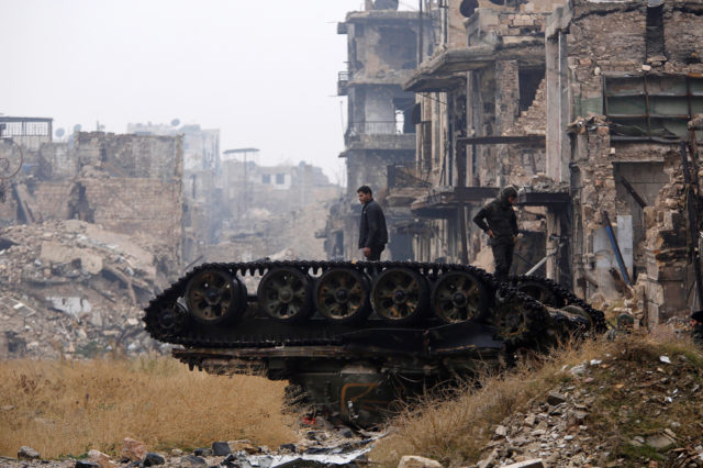 Forces loyal to Syria's President Bashar al-Assad stand atop a damaged tank near Umayyad mosque, in the government-controlled area of Aleppo, during a media tour, Syria December 13, 2016. (Reuters)