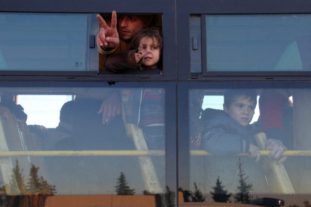 Syrians who were evacuated from rebel-held neighborhoods in Aleppo deliver a hopeful gesture as they arrive in the opposition-controlled Khan al-Aassal region, west of the city, Dec. 15, 2016. Hundreds of civilians and rebels left Aleppo under an evacuation deal that will allow Syria's regime to take full control of the city after years of fighting. (AFP)