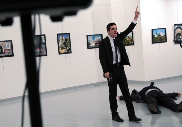 "A man identified as Mevlut Mert Altintas shouts after shooting Andrei Karlov, the Russian Ambassador to Turkey, at a photo gallery in Ankara, Turkey, Dec. 19, 2016. Shouting ""Don't forget Aleppo! Don't forget Syria!"" Altintas fatally shot Karlov in front of stunned onlookers at a photo exhibit. (AP)"