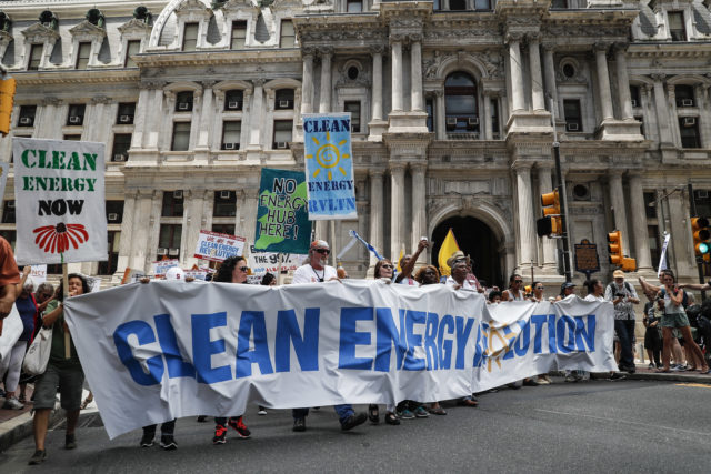 Climate change activists carry signs as they march during a protest in downtown on July 24, 2016, in Philadelphia, ahead of the start of the Democratic National Convention. (AP)