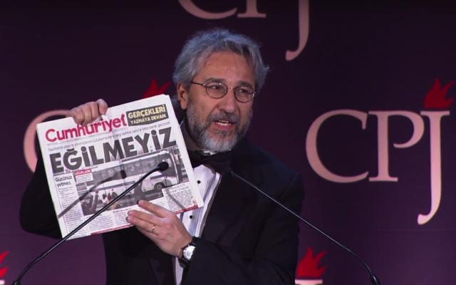 """Jan Dundar mukofotni qabul qilar ekan, """"Egilmaymiz"""" yozuvi bilan chiqqan """"Jumhuriyet"""" gazetasi nusxasini namoyish qildi"""