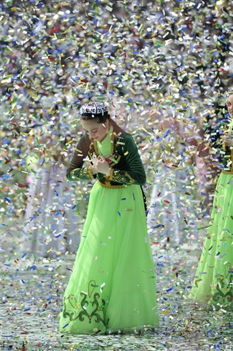 "Folk dancers in national costumes perform during the festivities marking the holiday of Navruz in Tashkent, Uzbekistan, Monday, March 21, 2011. Navruz, central Asia's spring ""New Year"" holiday, falls on March 21. (AP Photo/Anvar Ilyasov)"