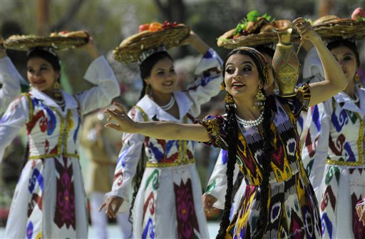 "Uzbek dancers in embroidered silk costumes perform during the festivities marking the Navruz holiday in Tashkent, Uzbekistan, Tuesday, March 19, 2013. Navruz (""New Year"") dates back to ancient Iranian and Central Asian fire-worshippers who celebrated the spring equinox with dances and ritual food. (AP Photo/Anvar Ilyasov)"